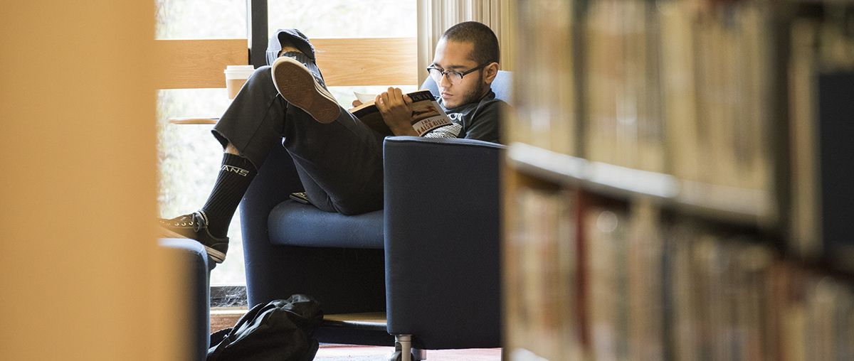 Student reading in library L